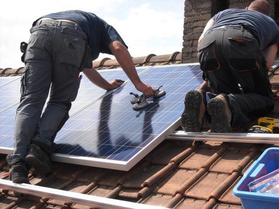 Homme posant un panneau solaire