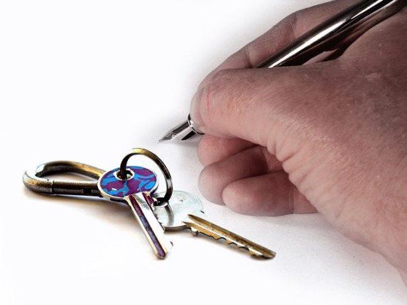 Main qui tient un stylo à côté de clés