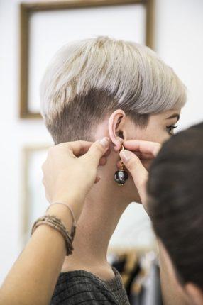 femme qui se fait accrocher une boucle d'oreille