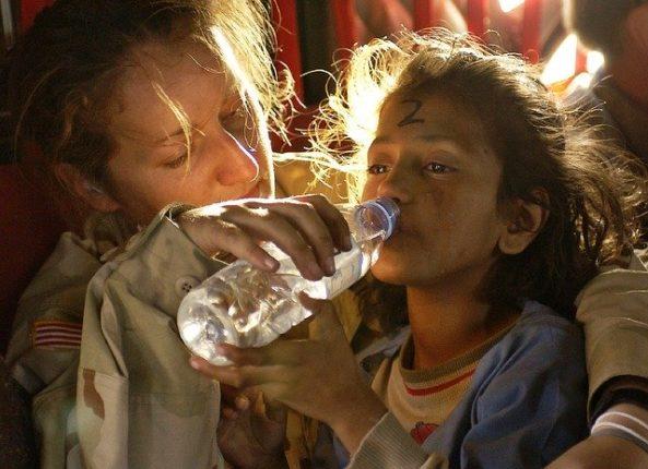 Femme qui donne de l'eau a un enfant assoifé